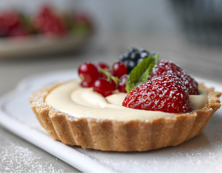 Cream and fruit filled pastry tart with raspberry, strawberry, blackberry and redcurrants, on plate with icing sugar