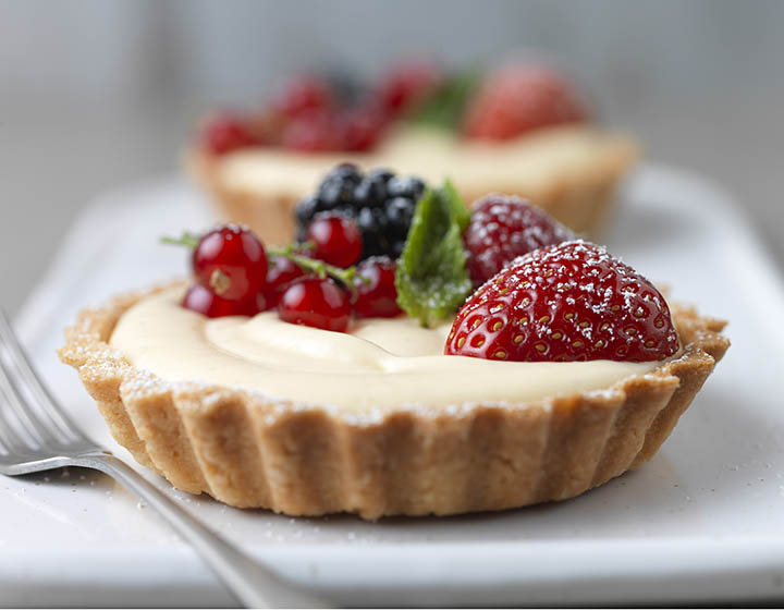 Cream and fruit filled pastry tart with raspberry, strawberry, blackberry and redcurrants, on plate with fork