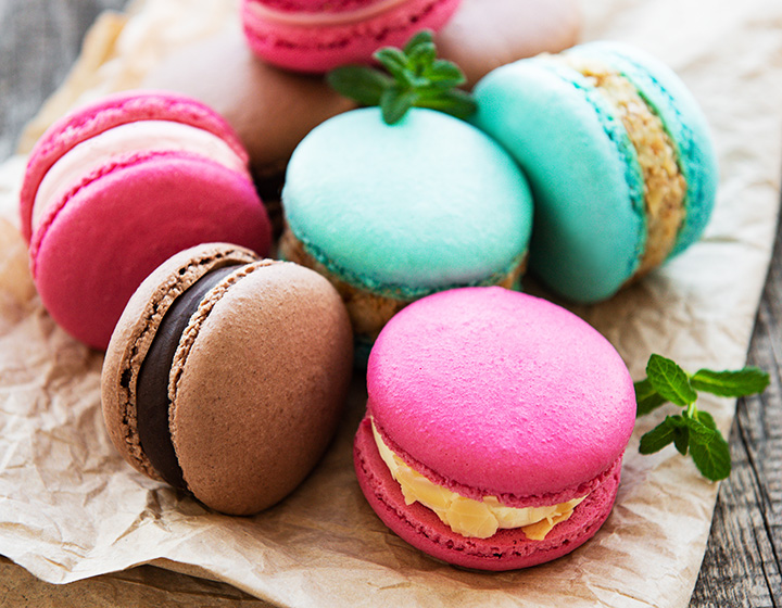 Colorful macaroons and mint on old wooden background