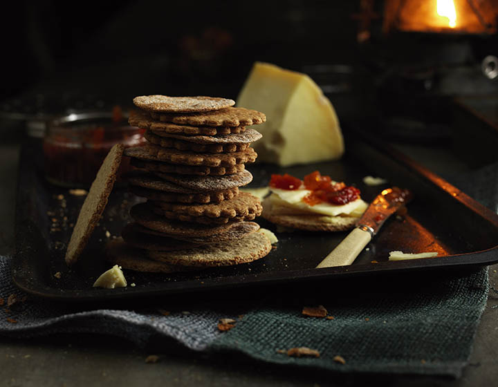 Pile of crackers with cheese, chutney and knife on a tray in front of fire