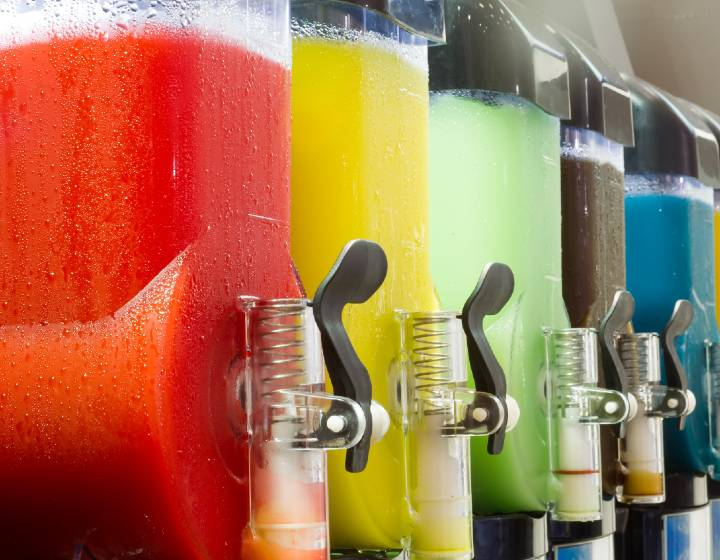 Row of slush machines filled with different brightly coloured drinks