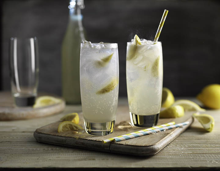 Two tall glasses of lemonade on a chopping board with ice, lemon and straws