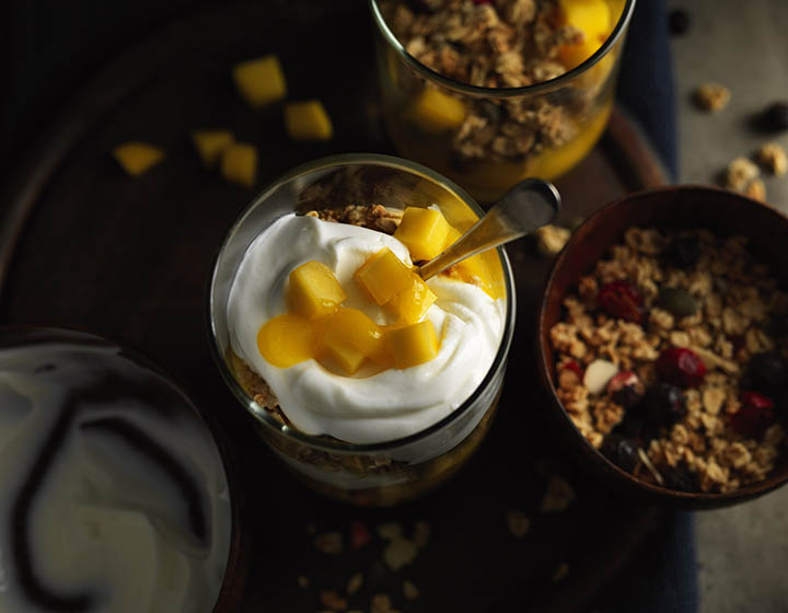 Yoghurt with yellow fruit and a bowl of granola