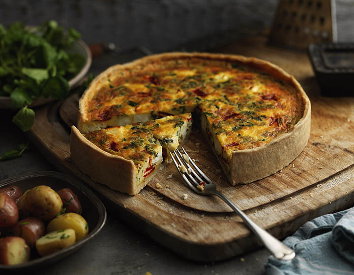A quiche with a fork and a slice missing