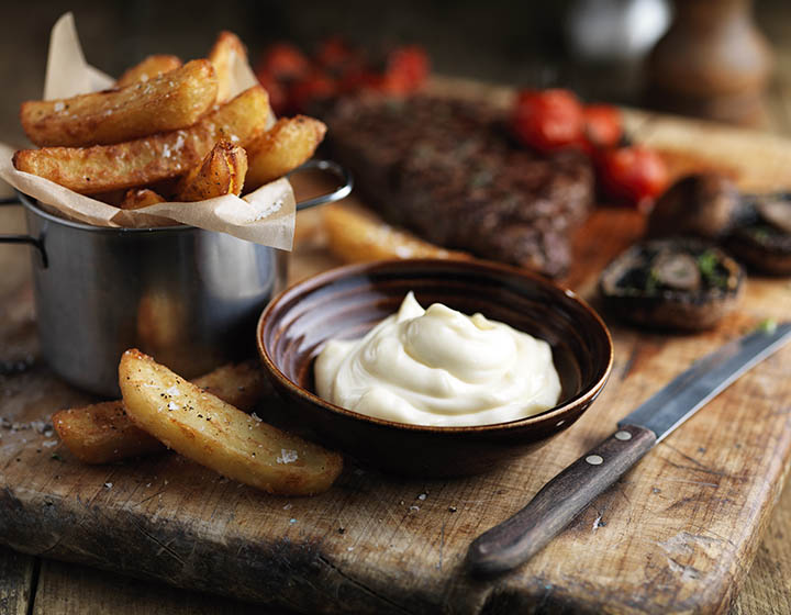 A bowl of mayonnaise surrounded by steak, chips and vegetables