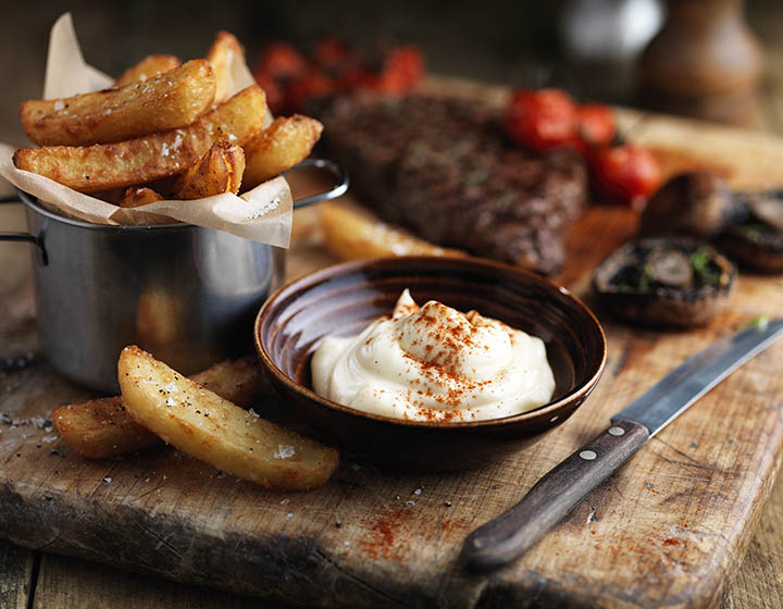 A chopping board covered in steak, tomatoes, chips and a bowl of mayonnaise
