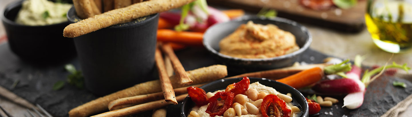 Antipasti plate with breadsticks, different flavours of hummus and fresh vegetables
