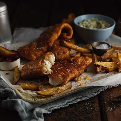 Fried fish and chips on a tray with tartar sauce